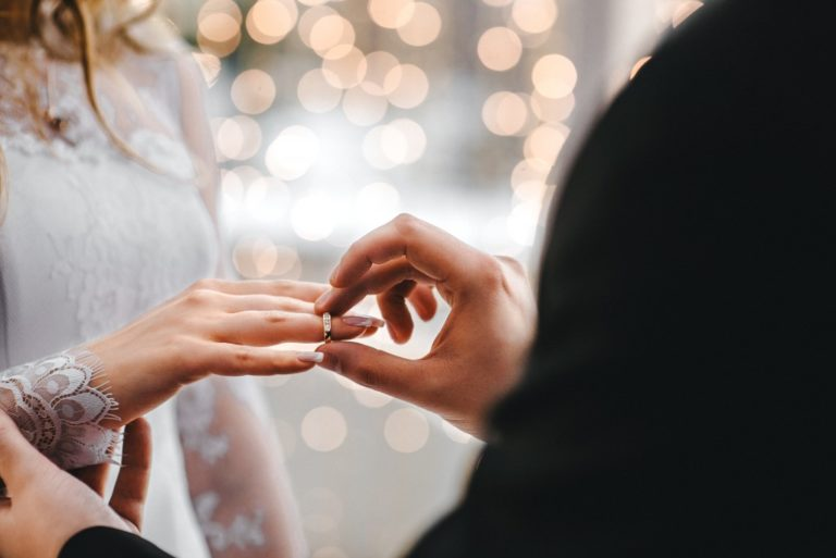 person putting a ring on her partner