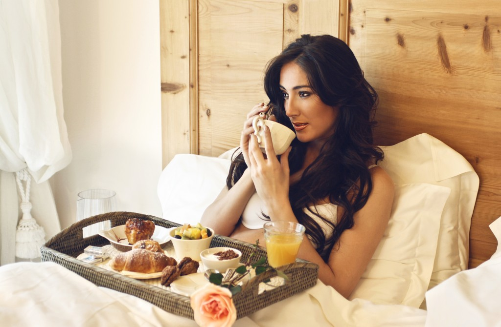 woman having breakfast in the hotel bed