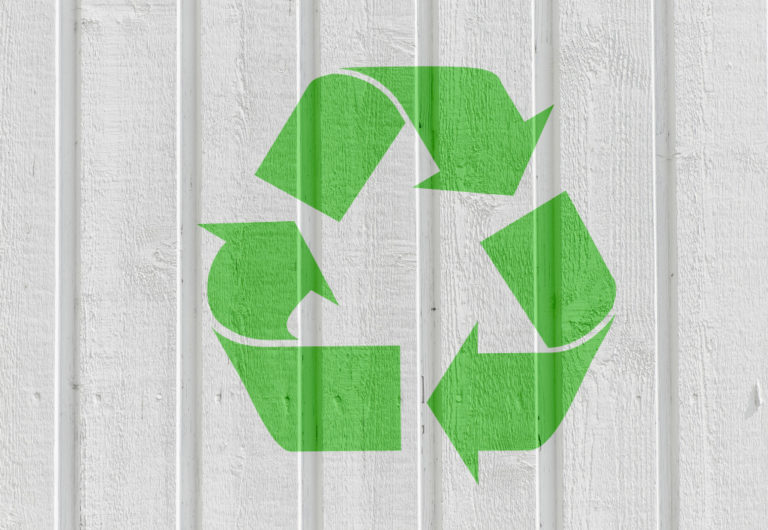 Recycling symbol on white wooden wall background.